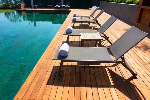 Liegestühle am hölzernen Dielenboden gegen Schwimmbad – Foto