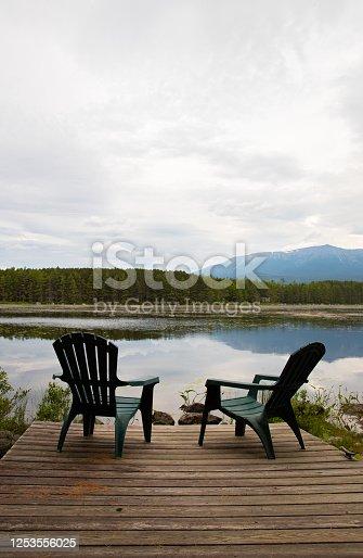 876420064 istock photo Deck Chairs Overlooking Mountain Lake 1253556025