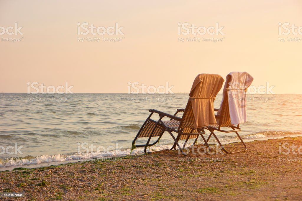 Deck chairs with towels on backrest on the seashore. stock photo