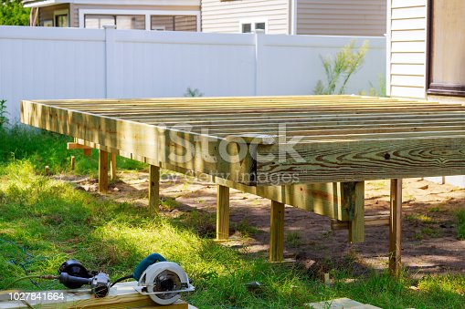 Deck construction work in garden with some torx circular saw, overlooking backyard landscape