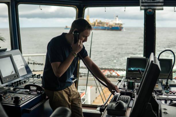 Officier de navigation de pont sur la passerelle de navigation. Il a l'air à travers des jumelles - Photo