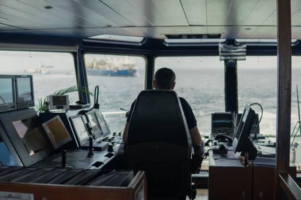 Officier de navigation de pont sur la passerelle de navigation. Il a l'air de la mer - Photo