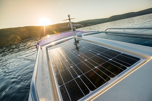 Deck of a luxury yacht with a solar panel moving on the blue sea during sunset