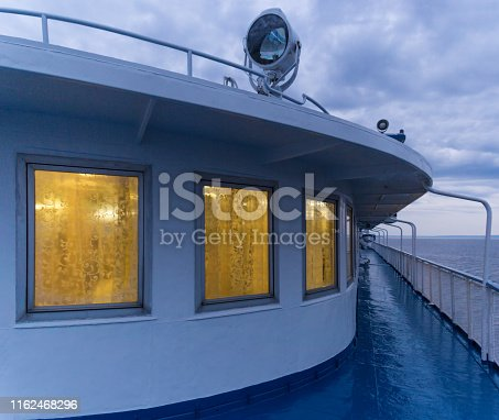 istock Deck of a passenger ship with luminous windows 1162468296