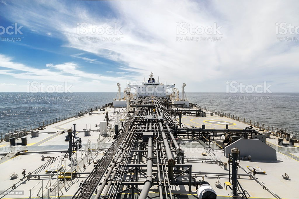 Deck of a new oil tanker in the sea under sky. View from the bow to...