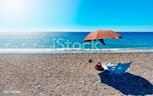 A deckchair under an umbrella facing the blue sea in a stony beach in Sicily, Italy. Summer holidays in Italian seaside resorts. Relax