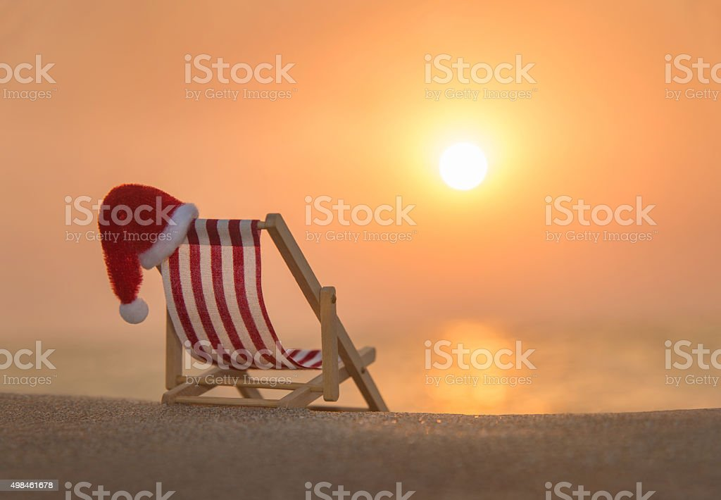 Deckchair with christmas santa hat at ocean beach during sunset stock photo