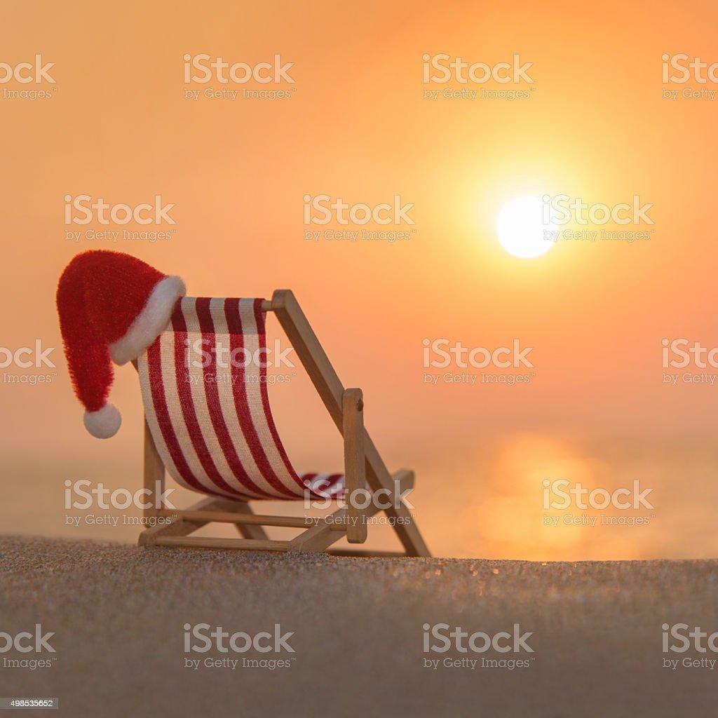 Deckchair with christmas santa hat at ocean beach during sunset stock photo