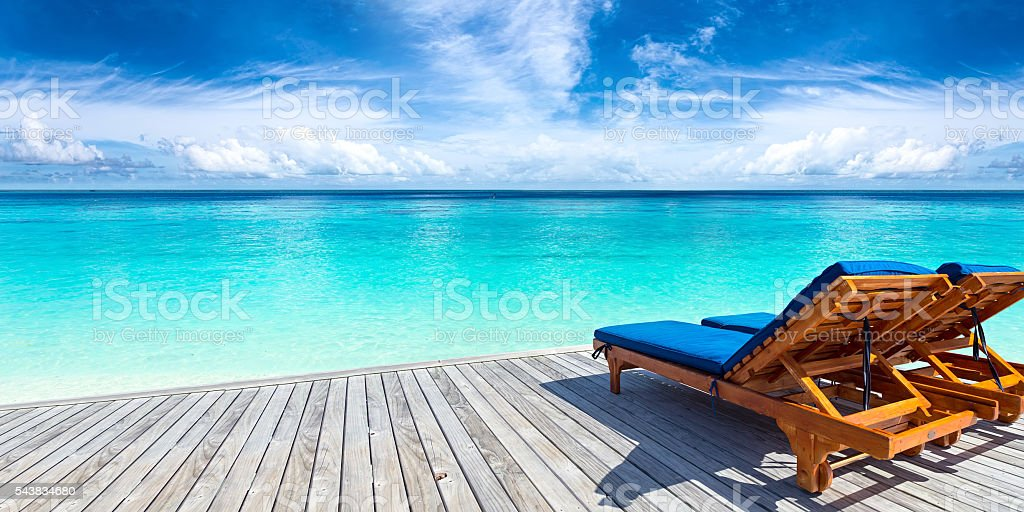deckchairs on jetty stock photo