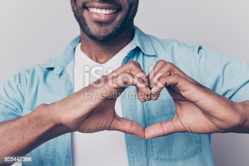 istock Declaration of love concept! Cropped close up view photo of cheerful loving sincere joyful charming attractive afro gut showing a heart using hands 925447366