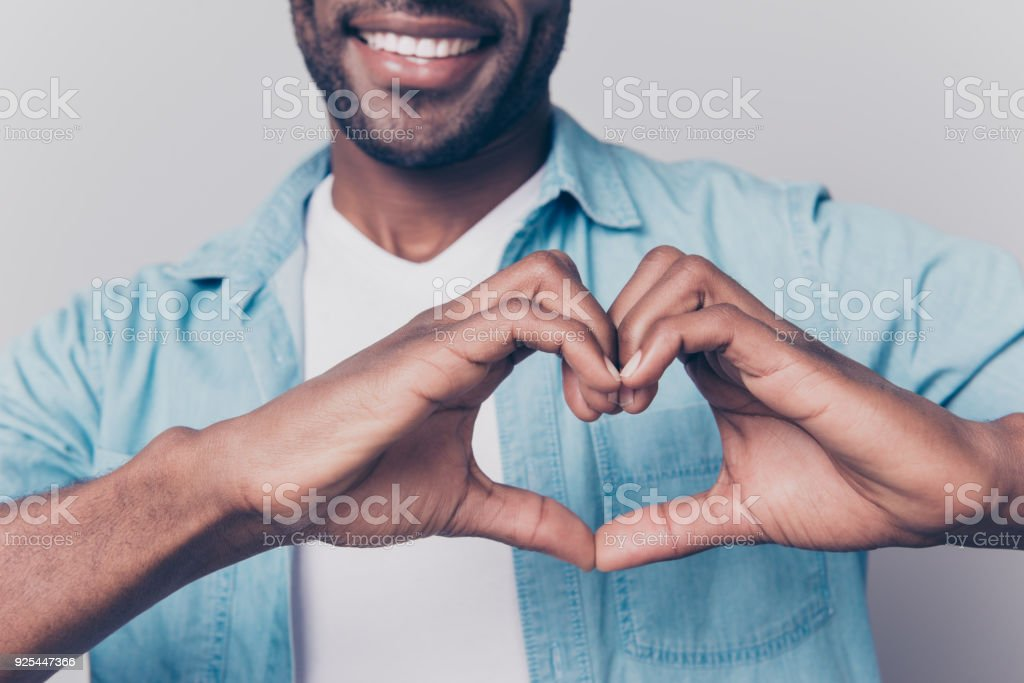 Declaration of love concept! Cropped close up view photo of cheerful loving sincere joyful charming attractive afro gut showing a heart using hands stock photo