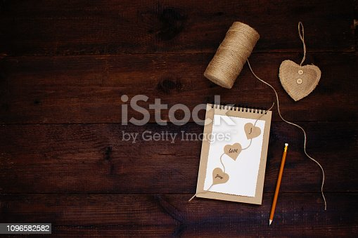 Declaration of love. Valentines day craft card ideas. Greeting card with text I LOVE YOU on craft recycled paper notebook, pencil, heart,  jute on wooden background. Love, romance, handmade concept