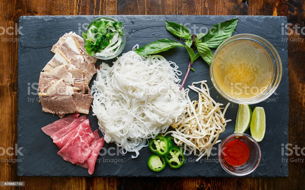 deconstructed pho laid out with all ingredients stock photo