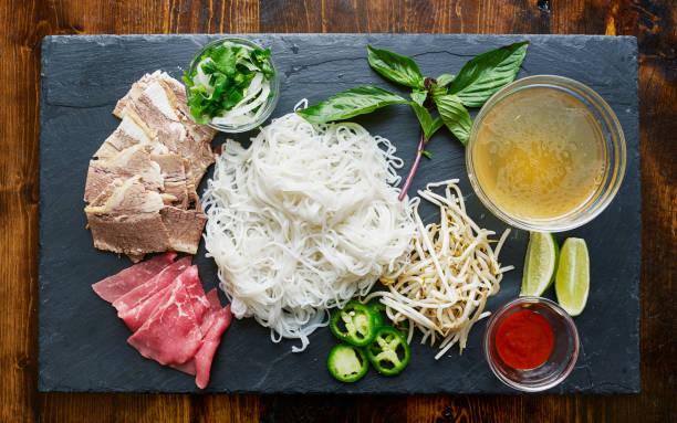 deconstructed pho laid out with all ingredients deconstructed pho laid out with all ingredients shot top down rice noodles stock pictures, royalty-free photos & images