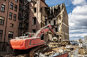 Deconstruction of a  building, excavator with grabber takes parts of building bit by bit