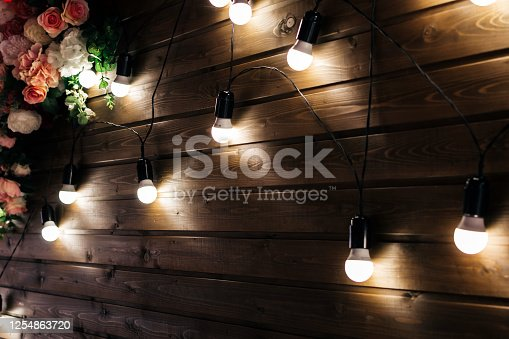 istock Decor of luminous lamps and flowers on a wooden wall background 1254863720