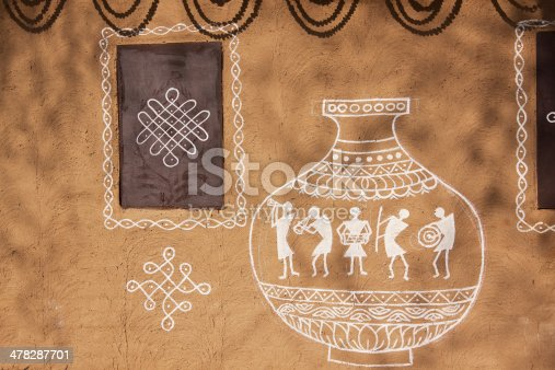 Ethnic adobe mud wall decorated with Old style village art work in white paint.