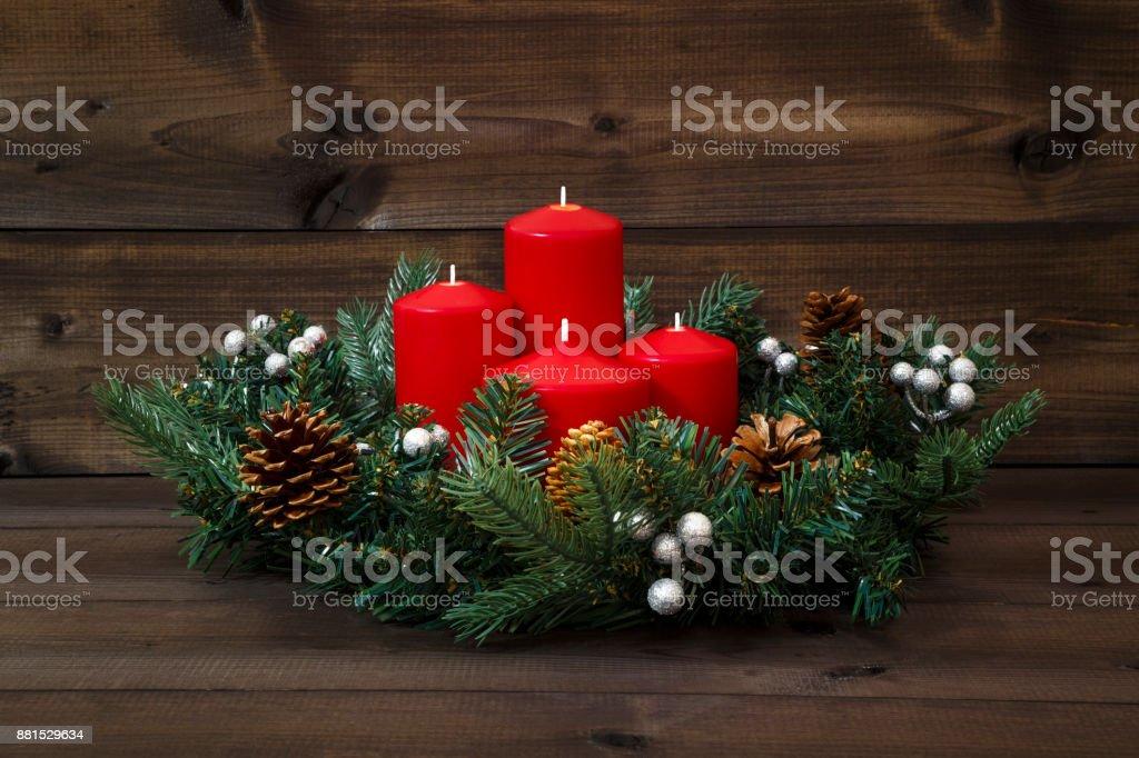 Adventskranz mit vier roten Kerzen auf einem hölzernen Hintergrund dekoriert – Foto