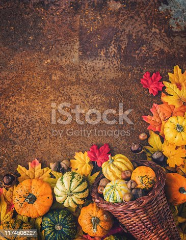 Decorated autumn cornucopia with pumpkins and leaves on the rustic background
