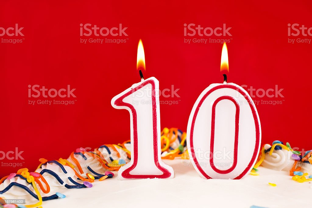 Decorated birthday cake with number 10 burning candles.  Red background stock photo