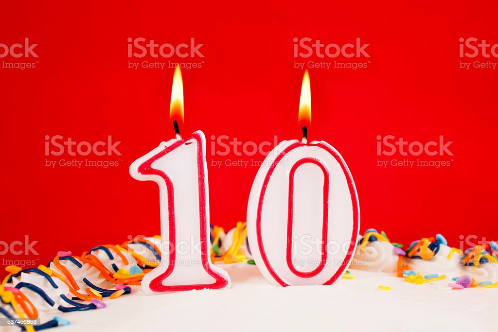 Decorated birthday cake with number 10 lit candles.  Red background. stock photo
