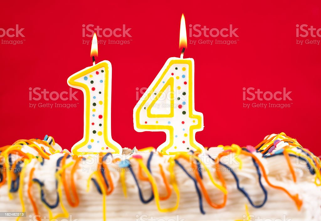 Decorated birthday cake with number 14 burning candles. Red background. stock photo