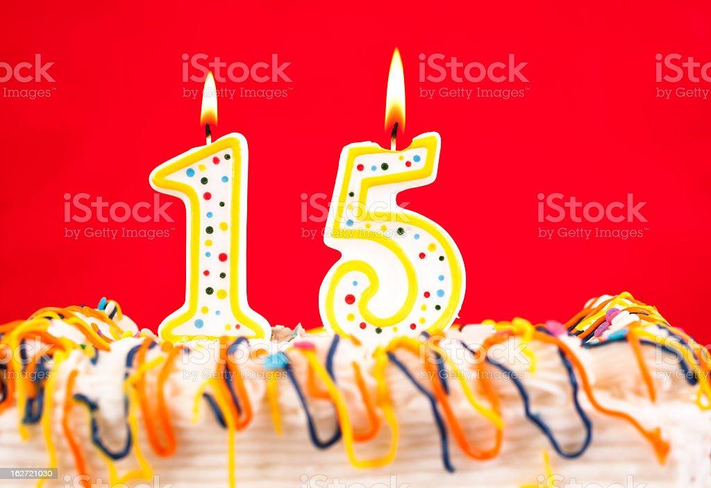 Das Geburtstagstorte mit brennenden Kerzen Nummer 15. Roter Hintergrund. – Foto