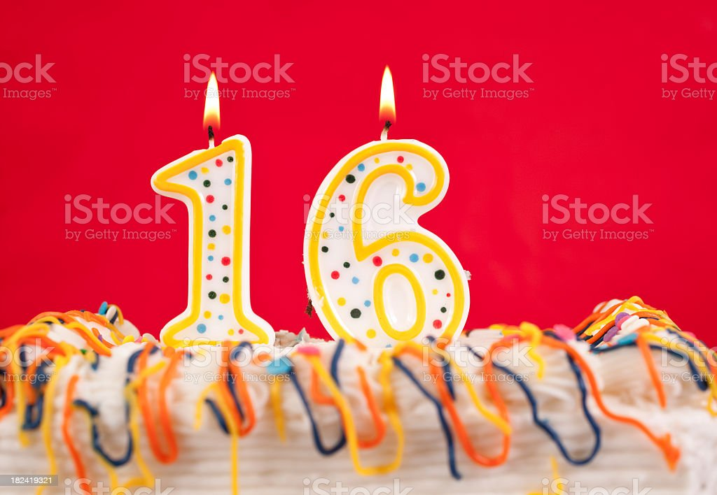 Decorated birthday cake with number 16 buring candles.  Red background stock photo