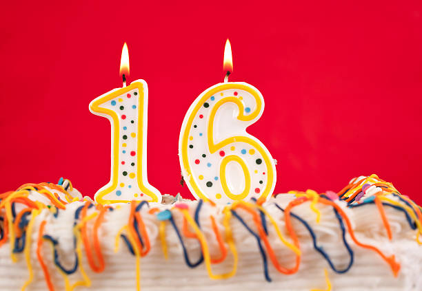 decorated birthday cake with number 16 buring candles.  red background - number 16 stock photos and pictures