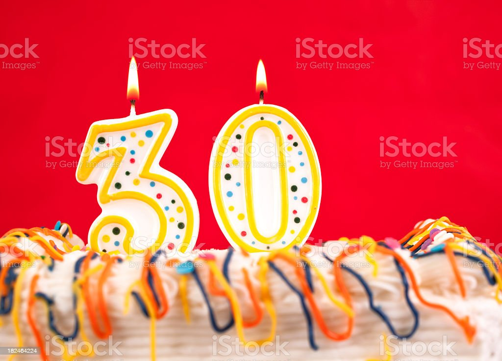 Decorated cake with number 30 burning candles. Red background