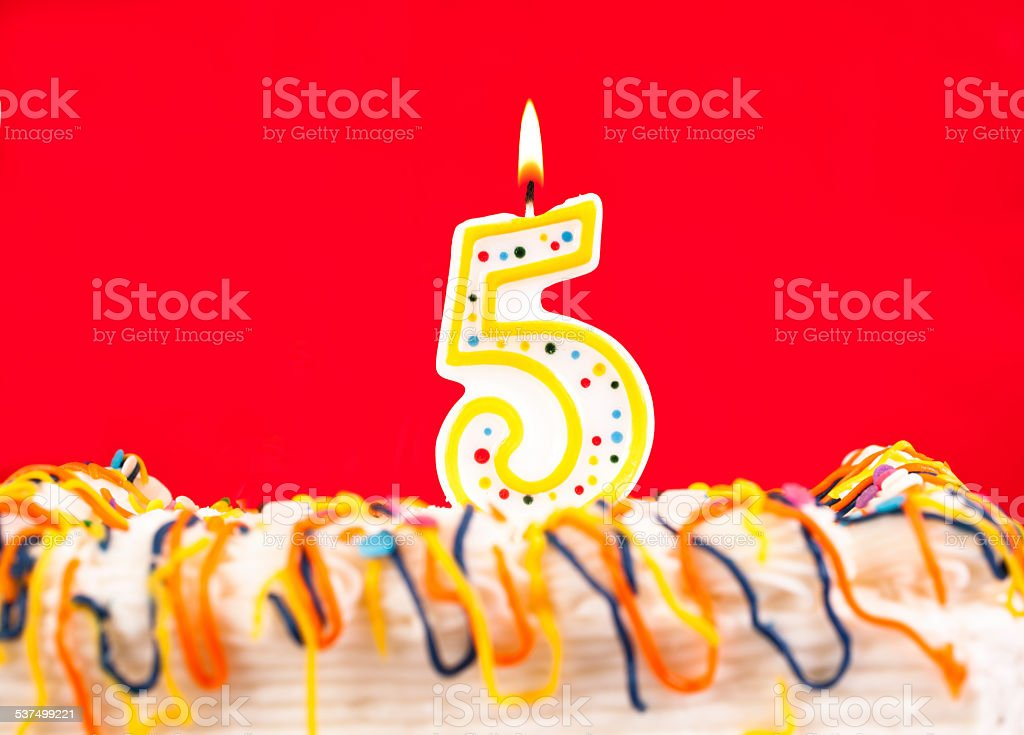 decorated birthday cake with number 5 lit candle red background