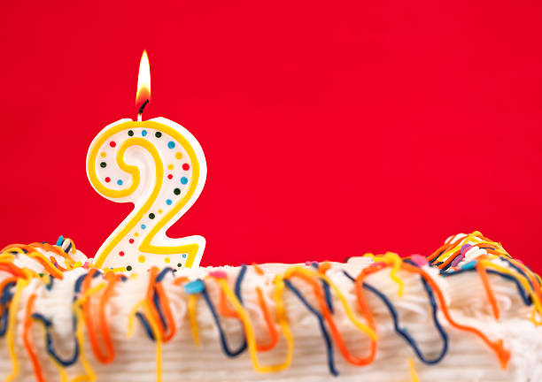 Decorated cake  with number 2 burning candles stock photo
