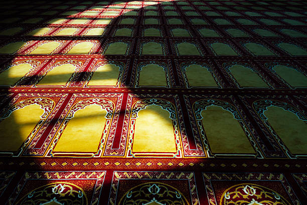 Decorated carpet of a mosque with sunlight to form crescent stock photo