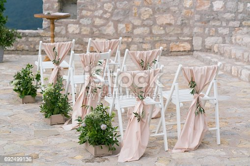 decorated chairs at the venue of the wedding ceremony