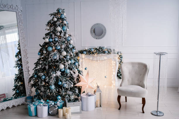 Decorated Christmas interior. Christmas tree with gifts boxes in a white room. Fir-tree, armchair, fireplace decorated with garlands. Decor. Happy New Year and Merry Christmas.