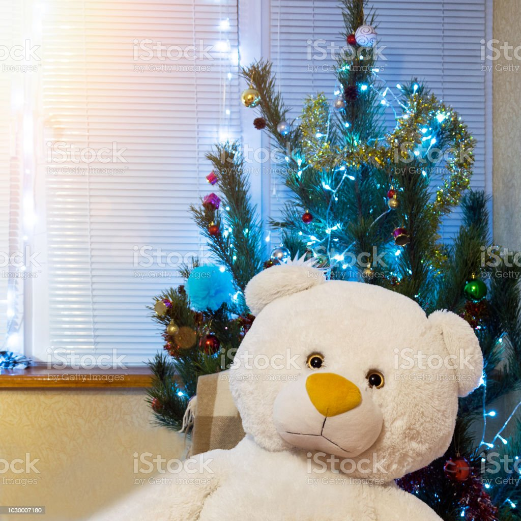 Decorated Christmas tree and big teddy bear. Cute New Year present...