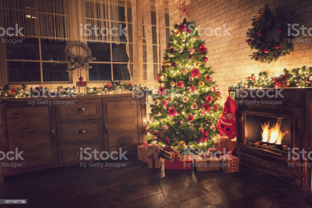 Decorated Christmas Tree Near Fireplace At Home Stock Photo