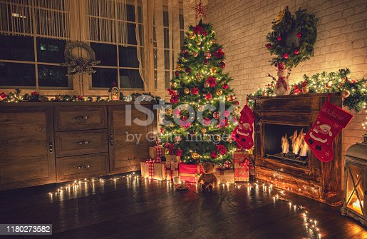 istock Decorated Christmas Tree Near Fireplace at Home 1180273582