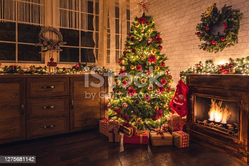 istock Decorated Christmas Tree Near Fireplace at Home 1275681142