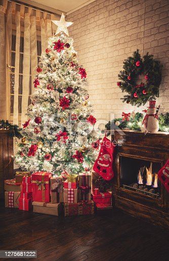 Christmas tree near fireplace in decorated living room