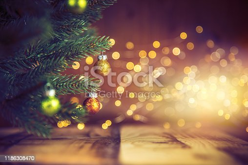Christmas tree decorated with golden & green ornaments on wood floor. Defocused lights in the background.