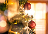Close up photo of decorated christmas tree in the middle of the living room.