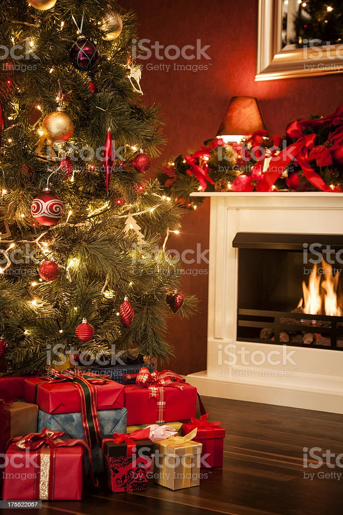 Decorated Christmas Tree with Ornaments, Presents and Fireplace royalty-free stock photo