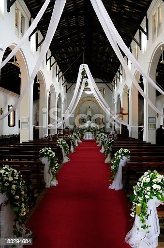 Flowers next to the aisle in a church before a wedding.