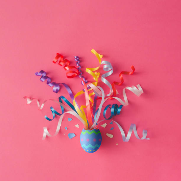 decorated easter egg with party streamers on pink background. easter concept. flat lay. - easter foto e immagini stock