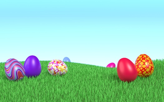 Cute decorated Easter eggs are lying on the grass under a clear blue sky. Easy to crop for all social media and print design sizes.
