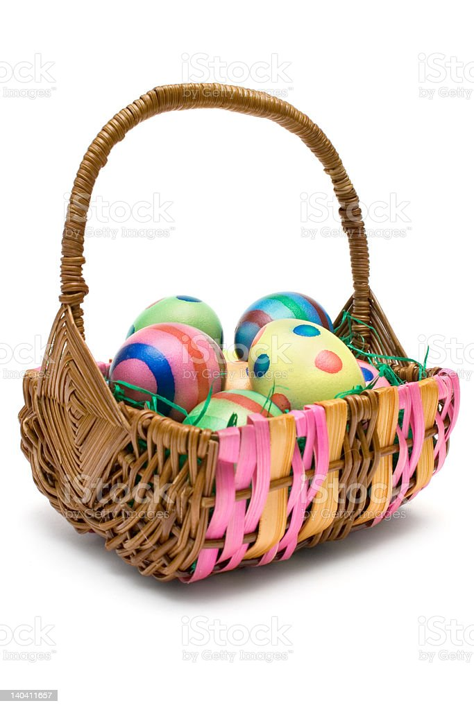 Decorated Easter eggs in a small wicker basket stock photo
