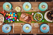 Decorated table for Easter celebration. On the table is glazed ham,painted eggs,tulips and Easter cake. top-down composition