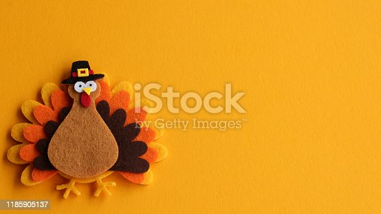 orange brown and yellow crafted felt turkey wearing pilgrim hat laying flat on an orange background with copy space