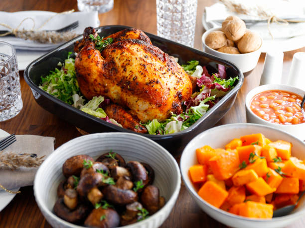 Decorated festive table with whole roasted chicken, salad, pumpkin, beans and walnut. The concept of family dinner or Thanksgiving celebrate. stock photo